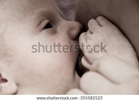 Photo of the Young mother breastfeeding her baby boy