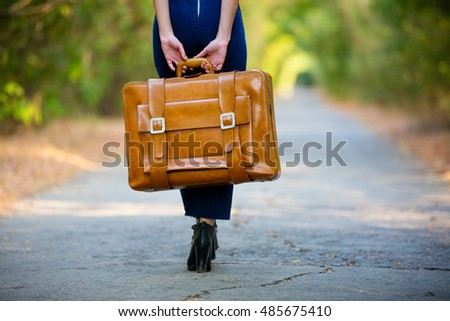 photo of the young woman with suitcase standing in the middle of the road