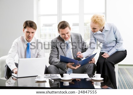 Photo of three employees planning their work together in office