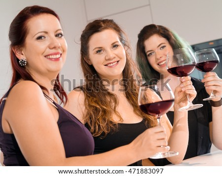Photo of three female friends toasting with red wine at a party. Focus on middle woman.