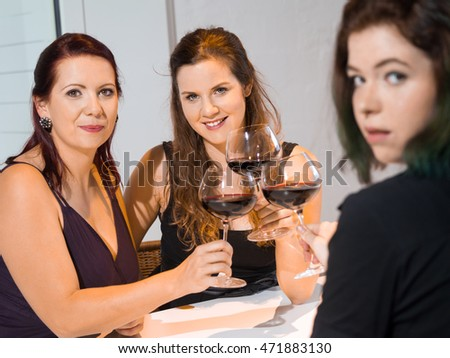 Photo of three female friends toasting with red wine in the kitchen. Focus on middle woman.