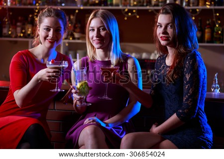 Photo of three happy female friends sitting at bar