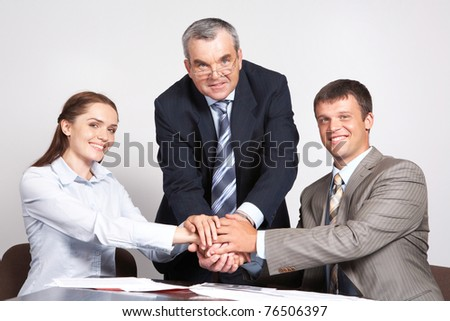 Photo of three partners putting their hands on the top - stock photo