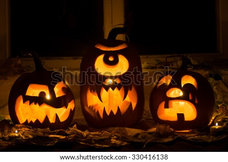Photo of three pumpkins for Halloween. Embittered, a Cyclops and the crying pumpkin against autumn leaves and candles - stock photo
