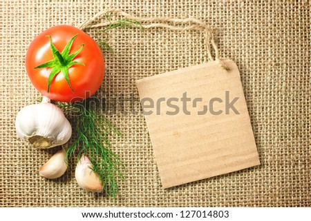 Photo of tomato and garlic vegetables and price tag on sacking background texture