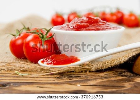 Photo of tomato ketchup in a spoon with cherry tomatoes
