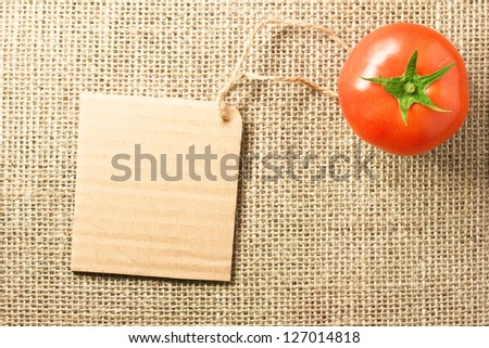 Photo of tomato vegetable and price tag on sacking background texture