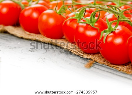 Photo of tomatoes on wooden board with white space