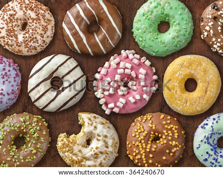 Photo of twelve different donuts over wood background. - stock photo