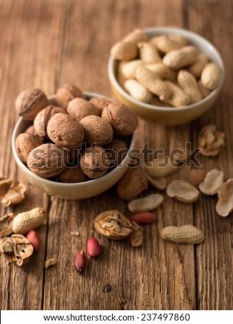 Photo of two bowls, one with walnuts and second with peanuts placed on old worn wooden table and with shells and nuts around captured from the top. - stock photo