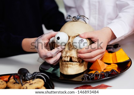 Photo of two boys hands holding spooky eyes just in skull eye-sockets - stock photo