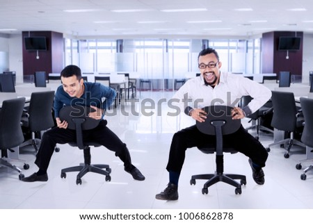 Photo of two businessmen looks excited while riding a chair and racing in the office