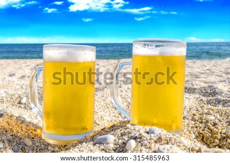 Photo of two cold beer bottle in the sand on the beach