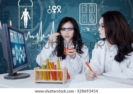 Photo of two college student doing experiment with chemical liquid in the test tube - stock photo