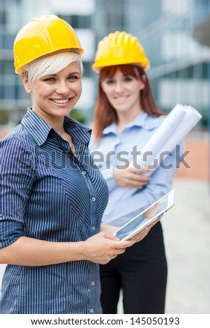 photo of two female constructors looking towards the camera