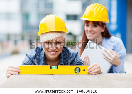 photo of two female constructors working with a level on a wall