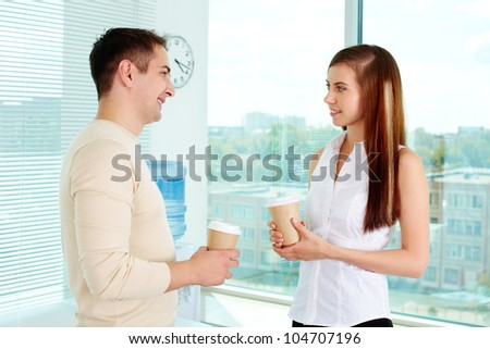 Photo of two friendly business partners in casual clothes talking in office