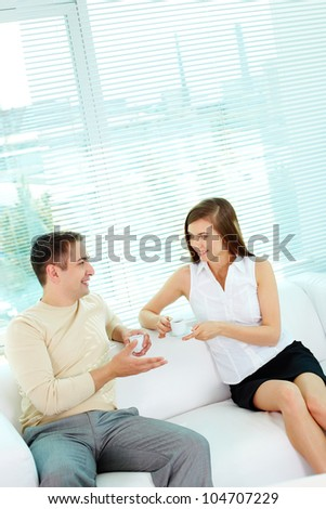 Photo of two friendly business partners in casual clothes talking while sitting in office