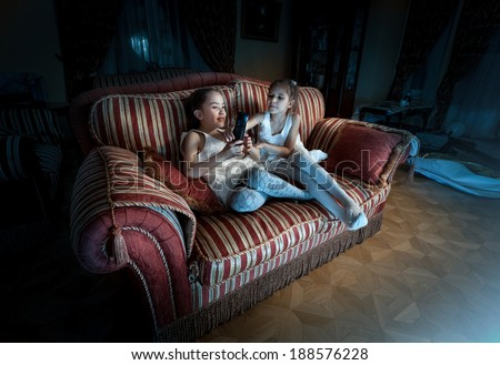 Photo of two girls fighting for TV remote on sofa at night - stock photo