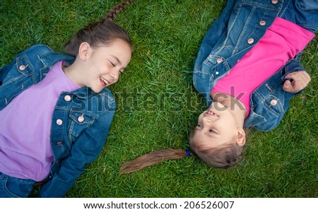 Photo of two little girls lying on grass face to face and laughing