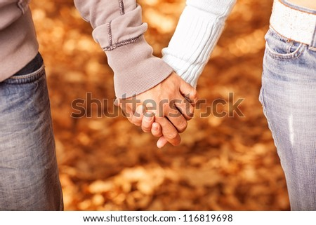 Photo of two loving people holding each other by hands on golden autumnal background - stock photo