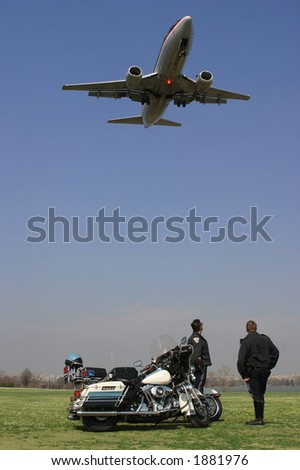 Photo of two motorcycle police watching a jet fly overhead as it is about to land.  Taken on location at Gravely Point Park near Ronald Reagan National Airport just outside of Washington, DC, USA. - stock photo