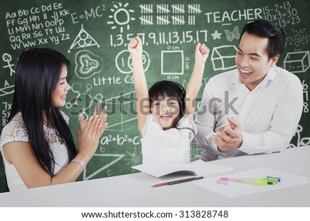 Photo of two proud and happy parents giving applause on their daughter after finishing schoolwork - stock photo
