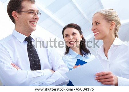 Photo of two smart women looking at their boss with smiles - stock photo