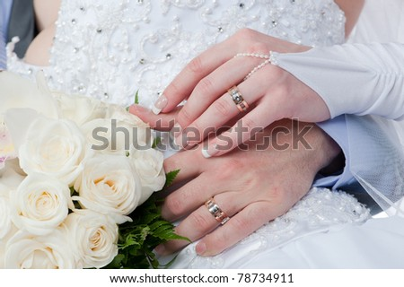 Photo of two tender hands of the groom and the bride with wedding rings and bouquet of white roses close up - stock photo