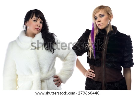 Photo of two women in fake fur coats on white background