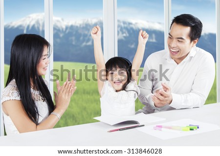 Photo of two young parents giving applause on their daughter after finishing school assignment at home - stock photo
