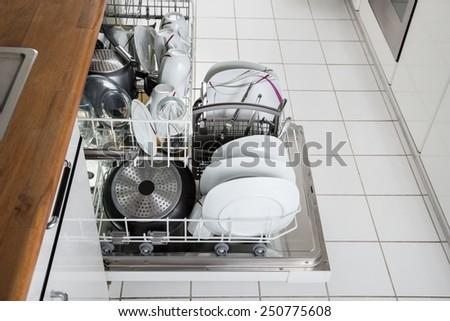 Photo Of Utensils Arranged In Dishwasher In Kitchen - stock photo