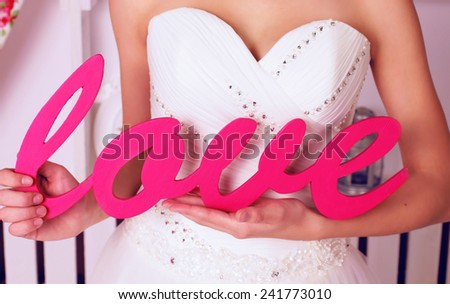 photo of  Valentine's Day,woman wearing in beautiful white evening dress and holding pink wooden word of love - stock photo