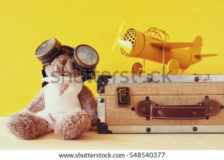 Photo of vintage toy plane and cute teddy bear on wooden table