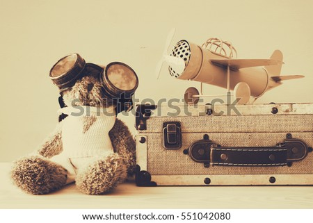 Photo of vintage toy plane and cute teddy bear on wooden table. Sepia style filtered image