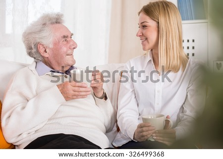 Photo of volunteer in care home talking with old man - stock photo