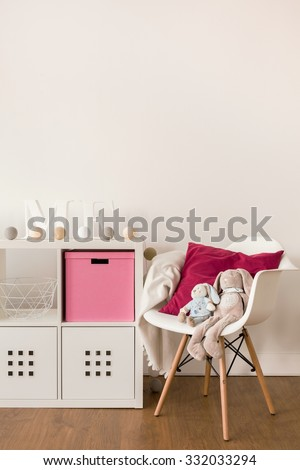 Photo of white cabinet and chair in child bedroom - stock photo