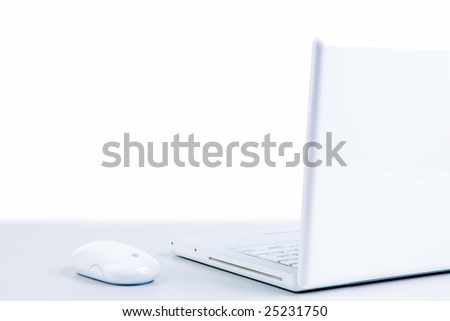 Photo of white cordless laptop with mouse of the same color near by - stock photo