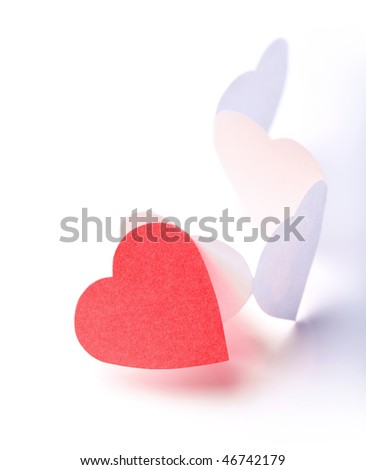 Photo of white paper hearts in chain with one of them red being over the others. - stock photo