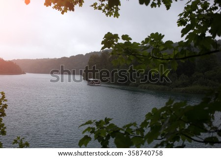 Photo of white vintage river motorboat inland water transport half light evening time summer silhouetted against green forest and clear sky on natural landscape background, horizontal picture - stock photo