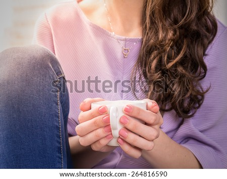 Photo of Woman in a pink Shirt Hold Coffee in vintage mug. Bright Sunny Background. Shallow DOF - stock photo