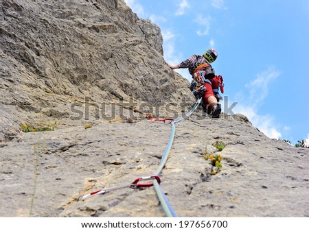 Photo of woman in sport wear climbing up mountain