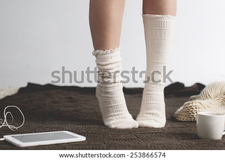 Photo of woman legs  with tablet and cup of coffee
