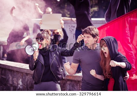 Photo of woman with megaphone and protesting couple - stock photo