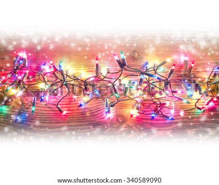 Photo of wooden board lit by Christmas light chain covered with snow; white space for text - stock photo