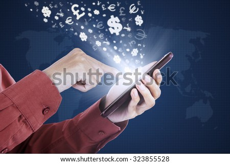 Photo of worker hand touching the mobile phone screen with currency symbols - stock photo