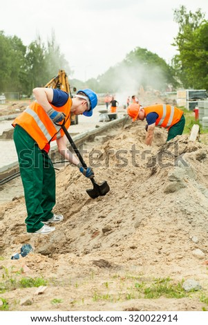 Photo of workers digging on a working platform - stock photo