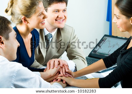 Photo of working team putting their hands on top of each other - stock photo