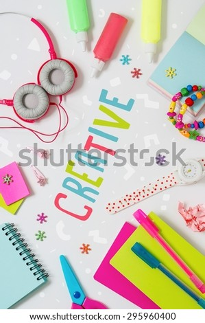 Photo of workplace with lots of stationery objects and headphones. Bright studio shot on light background. - stock photo