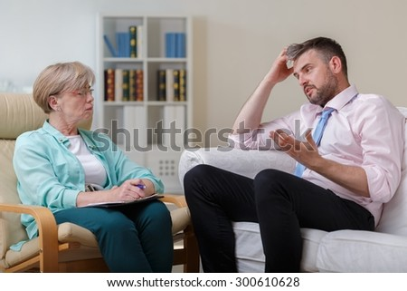 Photo of worried man on consultation with psychologist